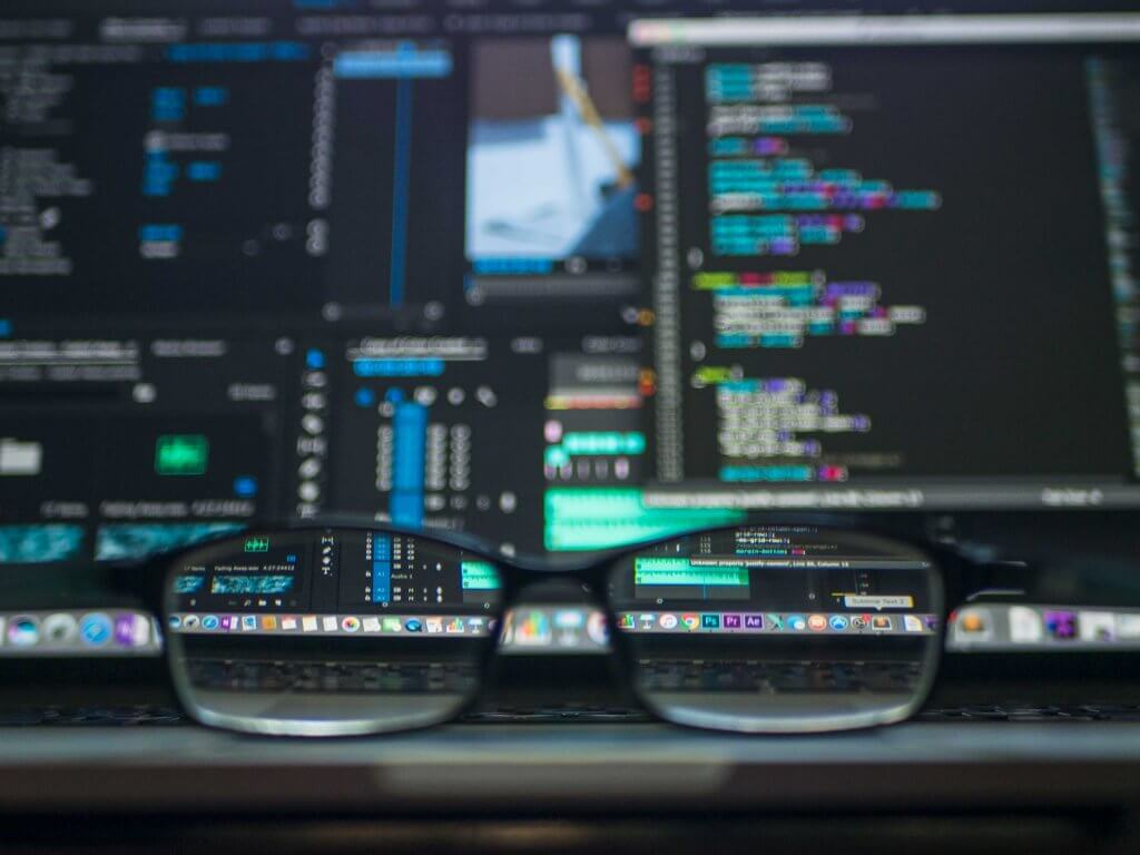 A pair of glasses in front of computer monitors